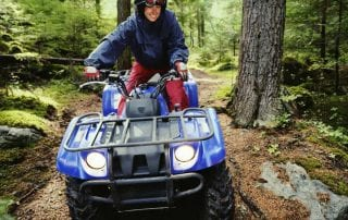 A grinning adventures prepares to take her next turn during a rugged ATV tour in Manitoba.